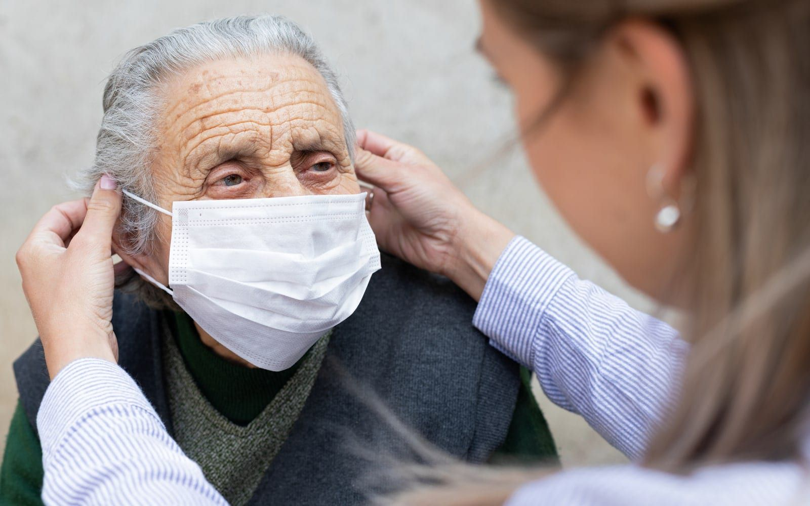 Doctor helping patient with mask