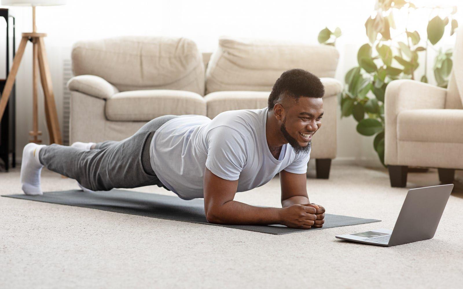 Man exercising using laptop video